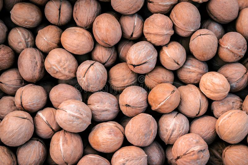 Top view heap of whole walnuts in supermarket, organic vegetables pattern and natural agricultural background with selective focus stock photography