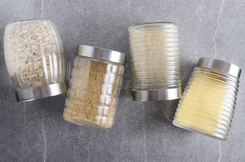 Top view of row of glass jars full of cereals on the grey kitchen table royalty free stock image