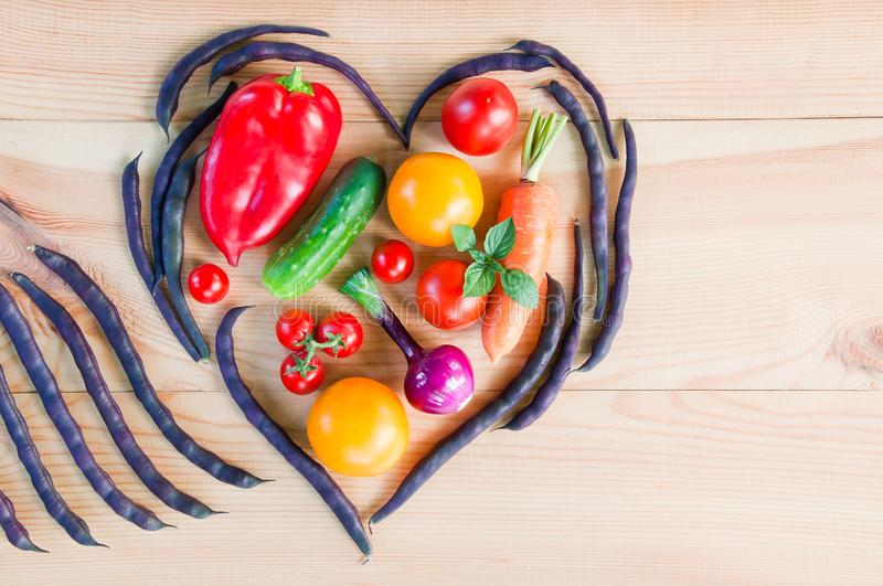 Top view of a heart made from pods of asparagus beans and fresh ripe vegetables on a wooden table royalty free stock images