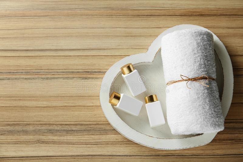 Top view of heart shaped tray with towel and cosmetic bottles on wooden table. Spa treatment. Top view of heart shaped tray with towel and cosmetic bottles on royalty free stock photography