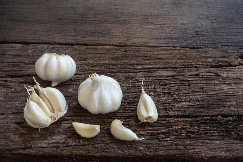Top view of herbal vegetable ingredients, fresh garlic, on old wooden table, cooking preparation concept. Top view of herbal vegetable ingredients, fresh garlic stock images
