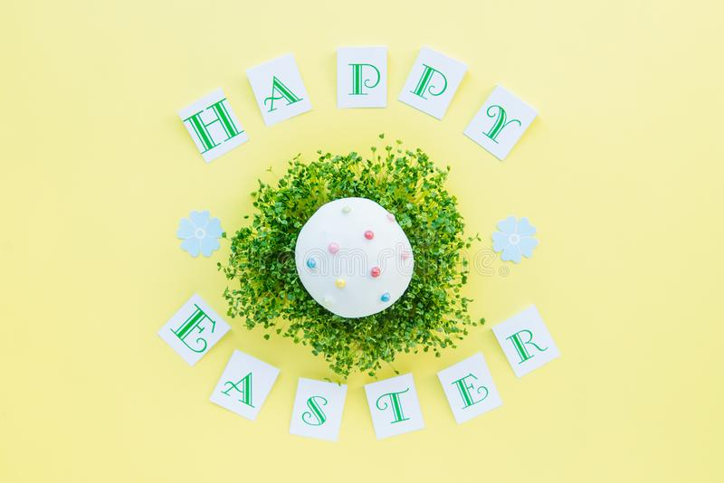 Top view holiday composition with green sprouts pillow and decorated easter cupcake on it, Happy Easter calligraphy lettering on b royalty free stock photo