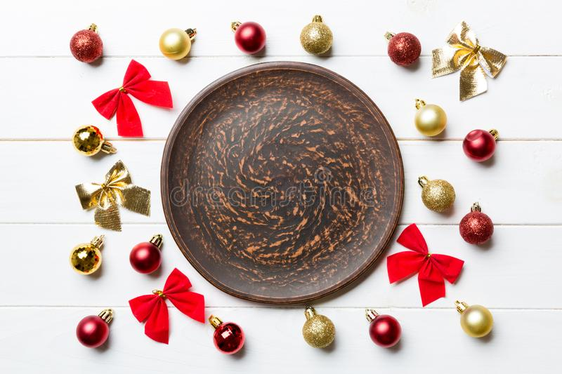 Top view of holiday dinner on wooden background. Plate, baubles and bows. Christmas Eve concept.  stock photography