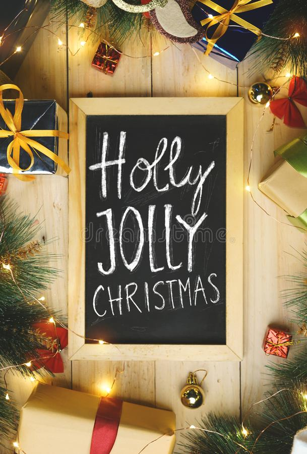 Top View of Holly Jolly Christmas Typography on Blackboard Surrounded By Christmas Gifts Ornament royalty free stock photography