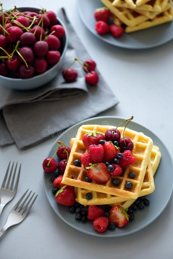 Top view on homemade belgian waffles with berries on gray table. Healthy breakfast concept royalty free stock image