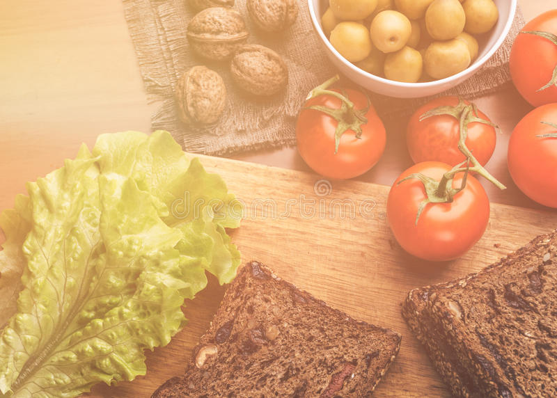 Top view. Homemade bread on wooden board, fresh tomatoes, olives in bowl,walnuts royalty free stock images