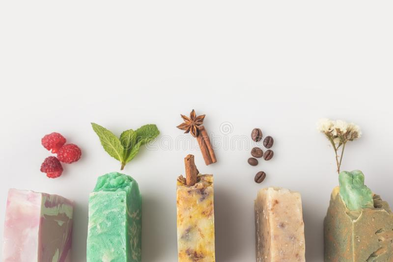 Homemade soap with different ingredient. Top view of homemade soap with different ingredients on white surface royalty free stock photo