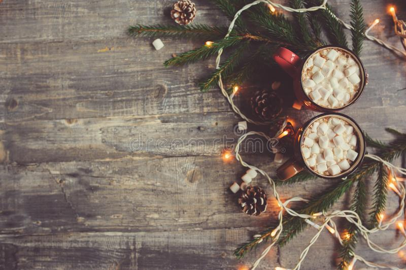 Top view of hot cocoa with marshmallows on rustic wooden table with christmas lights. Cozy winter home concept stock images