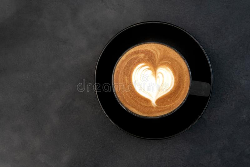 Top view of hot coffee cappuccino latte art heart shape foam in black cup on dark table background royalty free stock images