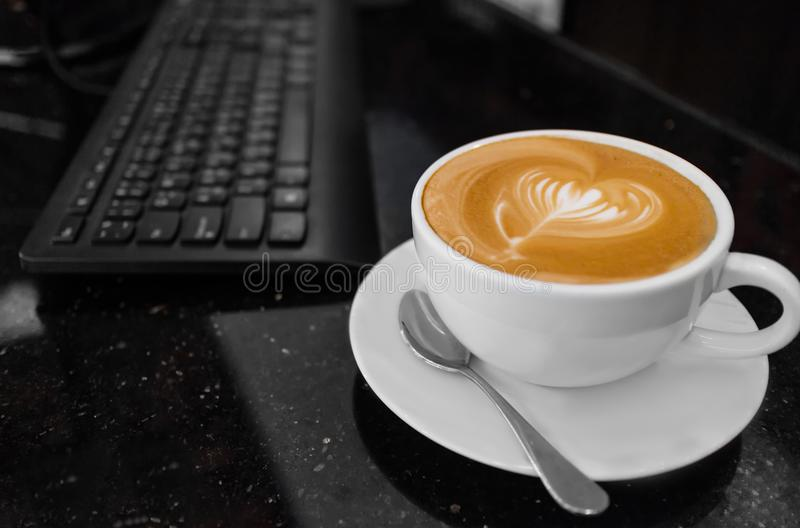 Top view of hot coffee cappuccino latte art in white ceramic cup on meeting table. Coffee shop stock photo