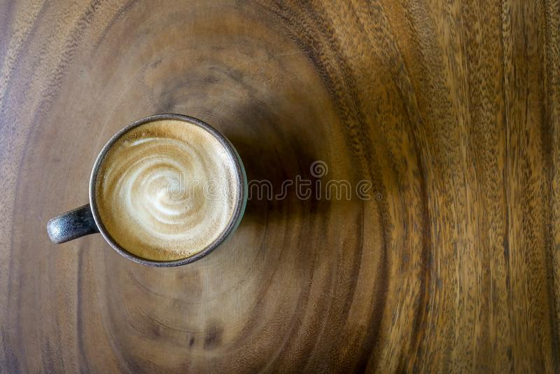 Top view of hot coffee cappuccino latte with stirred spiral milk foam in green ceramic cup on beautiful wood texture annual ring stock photos