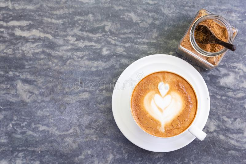 Top view of hot coffee with heart pattern in white cup and brown sugar on stone table background royalty free stock photo