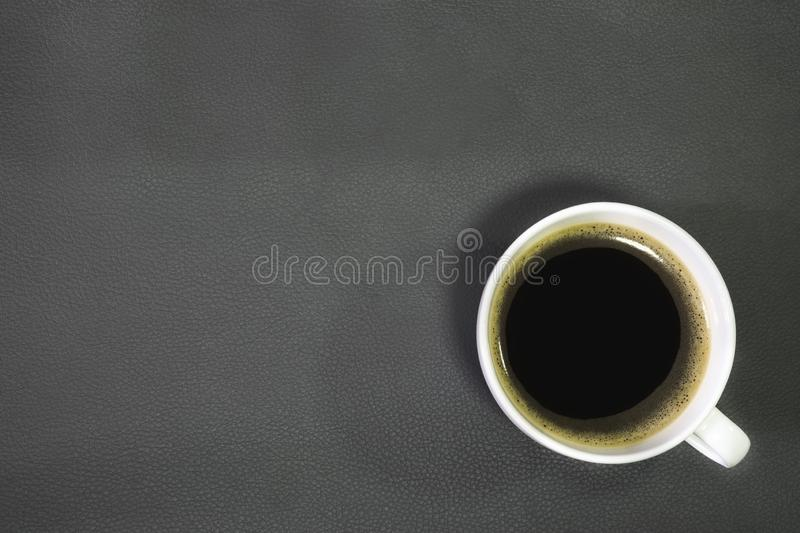 Top view of hot fresh black coffee in a white ceramic cup on leather texture background. top view. With copy space stock images