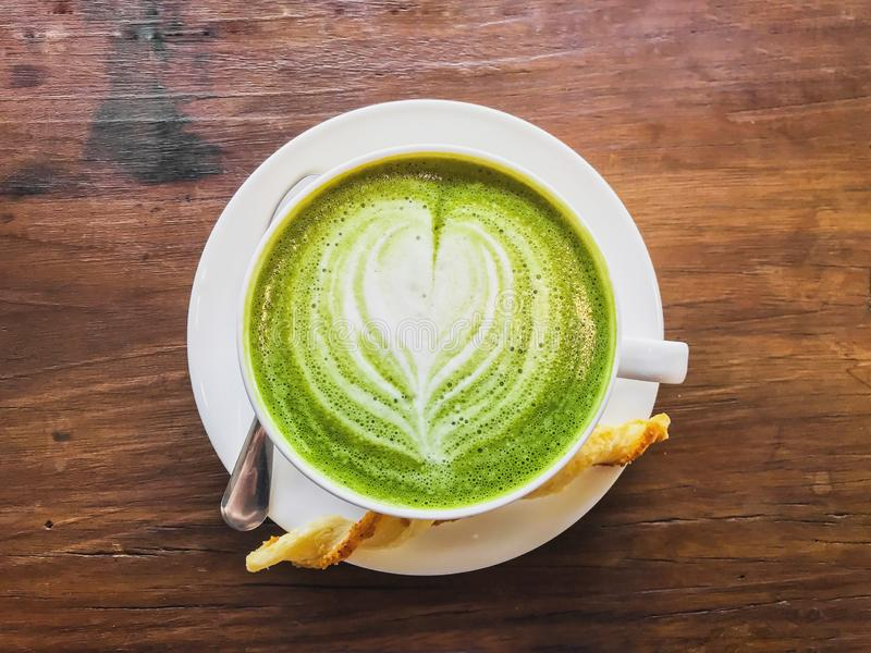Top view of Hot matcha green tea milk latte with creamy milk is heart-shaped pattern, a little sugar, bread and teaspoon in a cup royalty free stock photography