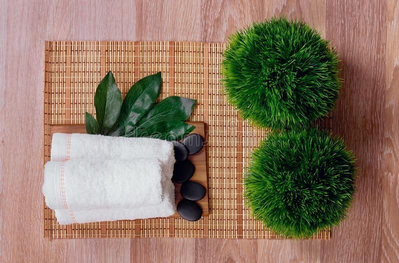 Top view of hot stones setting for massage treatment on blackboard with copy space.Towel, Salt, Plumeria Flower, Bowl for spa ther. Apy with Copy space royalty free stock images
