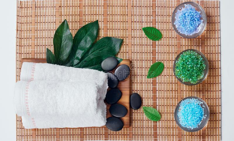 Top view of hot stones setting for massage treatment on blackboard with copy space.Towel, Salt, Plumeria Flower, Bowl for spa ther. Apy with Copy space royalty free stock photos