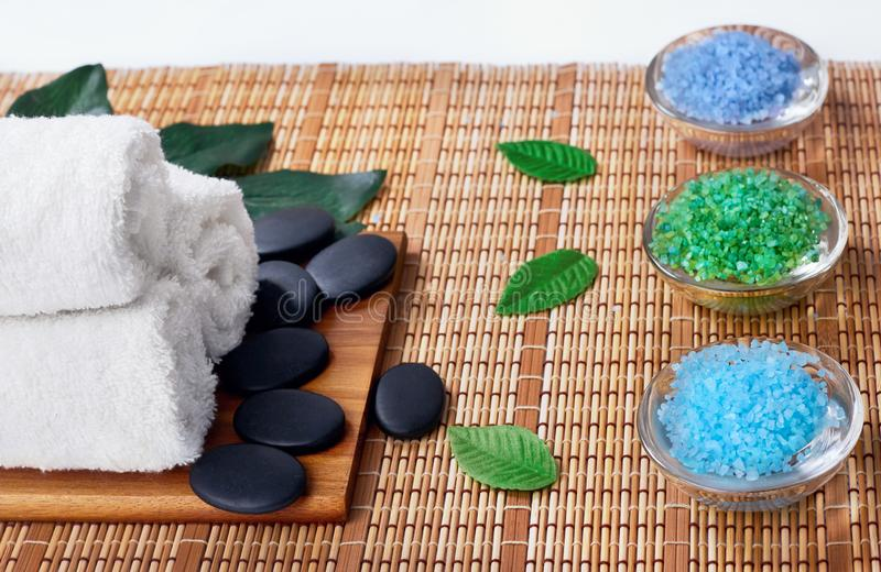 Top view of hot stones setting for massage treatment on blackboard with copy space.Towel, Salt, Plumeria Flower, Bowl for spa ther. Apy with Copy space royalty free stock image