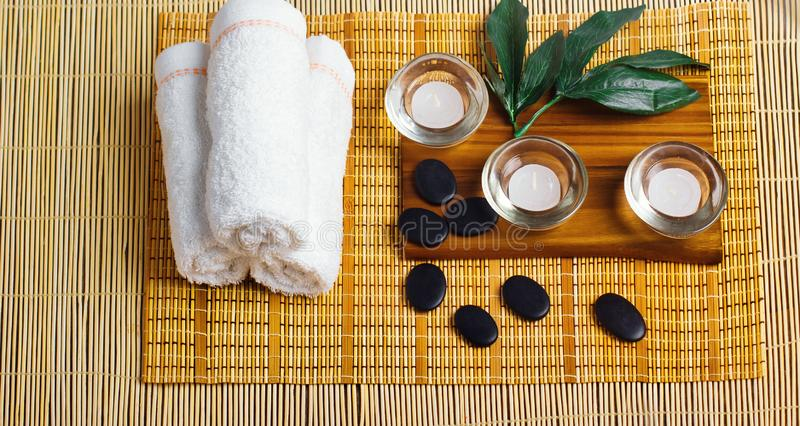 Top view of hot stones setting for massage treatment on blackboard with copy space.Towel, Salt, Plumeria Flower, Bowl for spa ther. Apy with Copy space stock photos