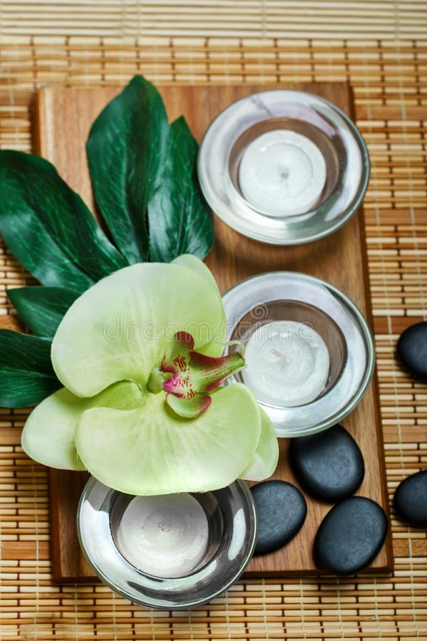 Top view of hot stones setting for massage treatment on blackboard with copy space.Towel, Salt, Plumeria Flower, Bowl for spa ther. Apy with Copy space stock image