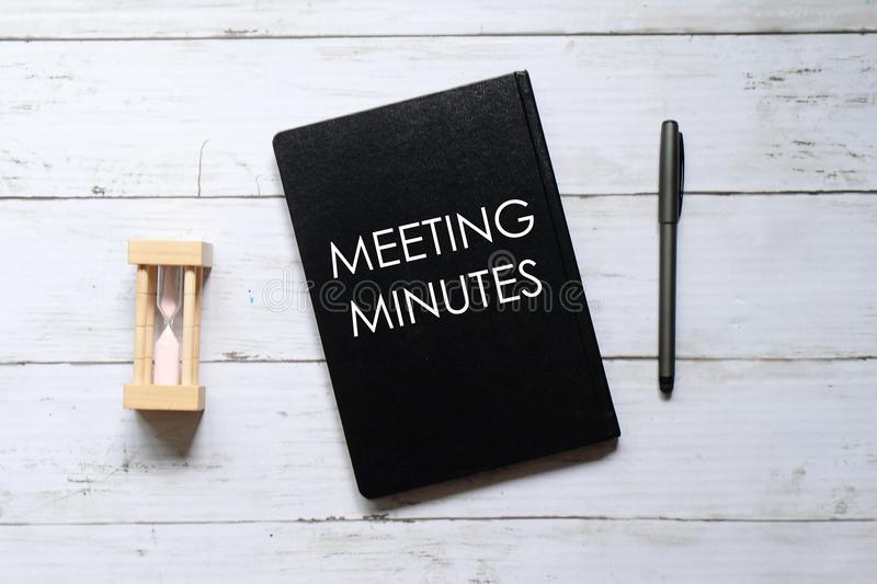 Top view of hour glass,pen and notebook written with 'MEETING MINUTES' on white wooden background royalty free stock photography
