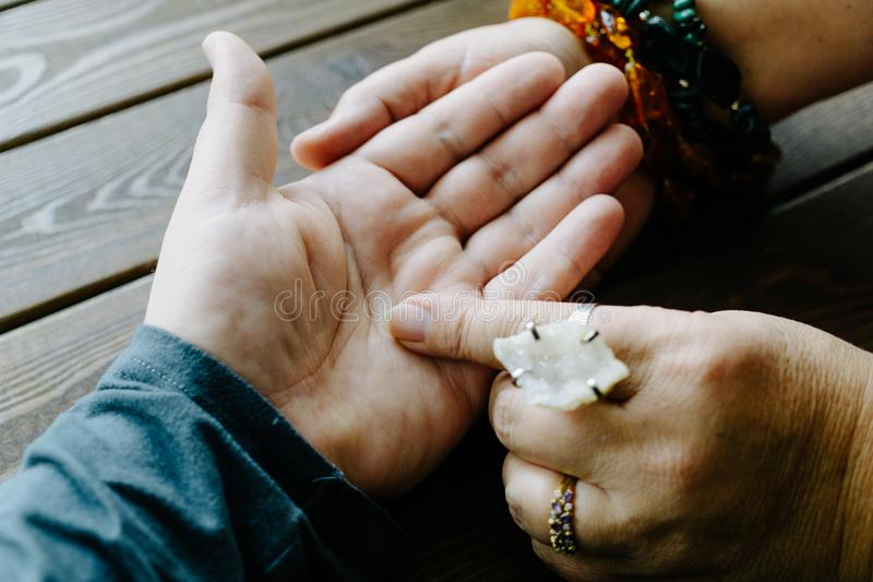 Top view of human hand and psychic or fortune teller explains lines on palm. Palmistry royalty free stock photo