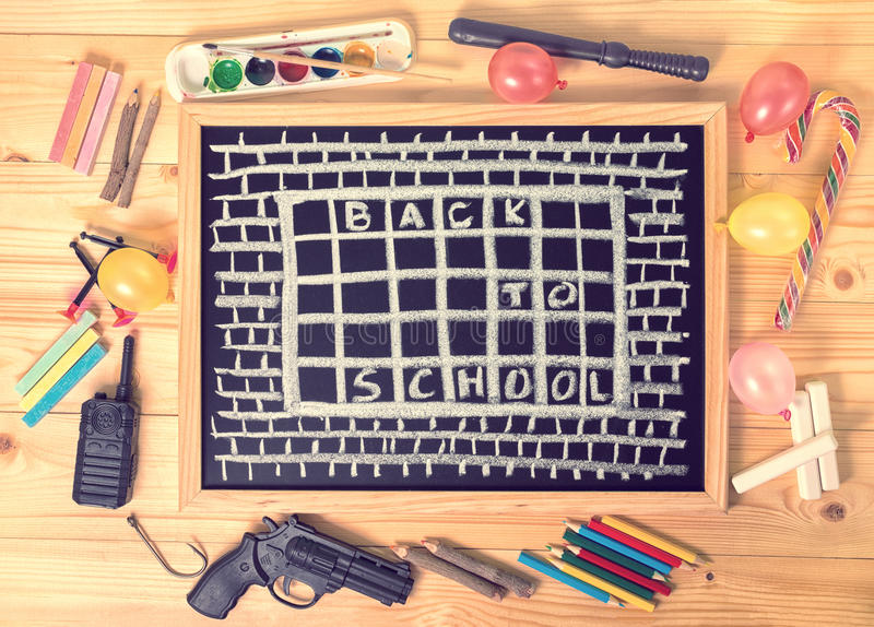 Top view humorous concept of hate school as prison with text back to school is written in chalkboard, chalks, toys and colorful p. Encils on wooden table, close royalty free stock photo