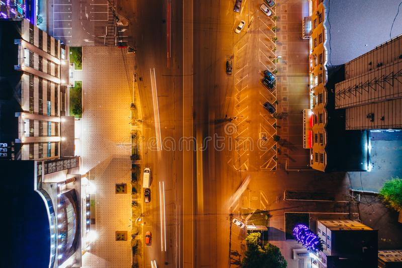 Top view of illuminated city road with car traffic and modern buildings, aerial drone photo royalty free stock photos