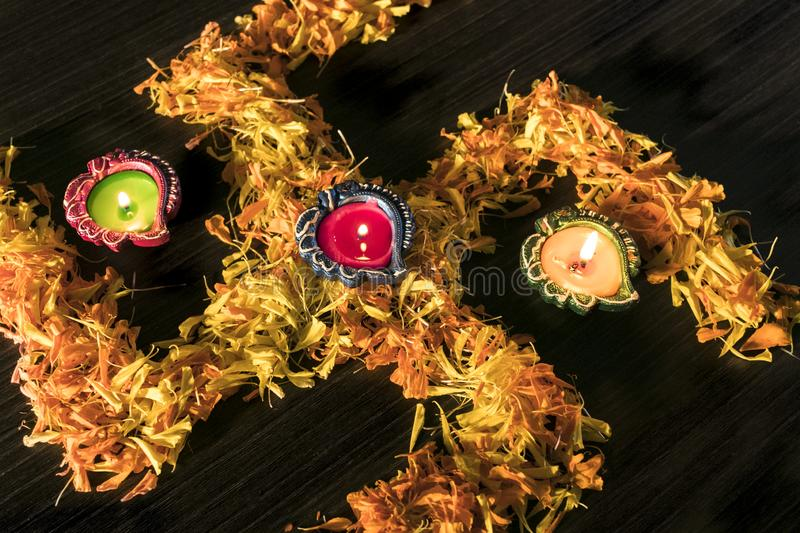 Dhanteras and diwali background.diwali greetings and wishes. A top view of illuminated diya placed on swastik to celebrate dhanteras and diwali festival royalty free stock photography