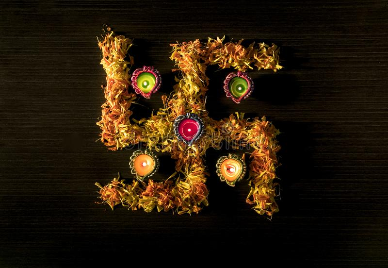 Dhanteras and diwali background.diwali greetings and wishes. A top view of illuminated diya placed on swastik to celebrate dhanteras and diwali festival royalty free stock photo