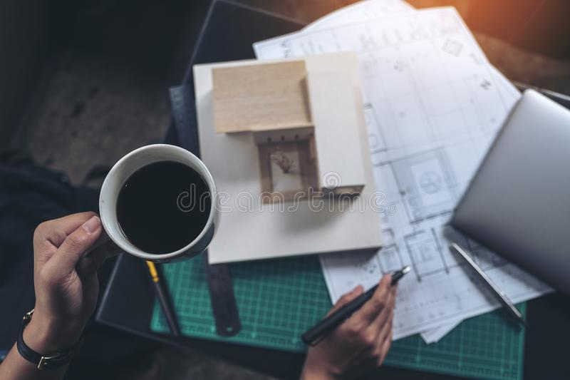 Top view image of an architects thinking and designing mass model while drinking hot coffee with shop drawing paper royalty free stock photography