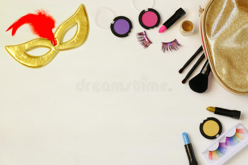 Top view image of carnival makeup. On white wooden background royalty free stock photo