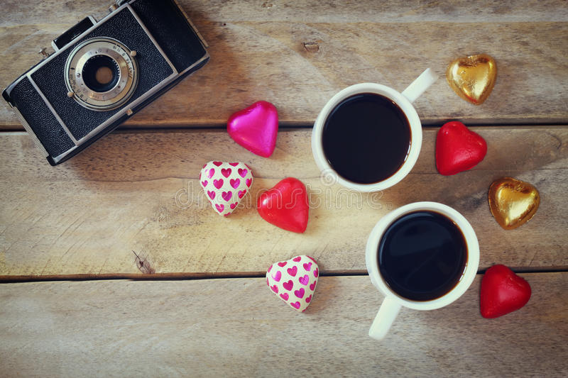 Top view image of colorful heart shape chocolates, fabric heart, vintage photo camera and cup of coffee on wooden table royalty free stock image