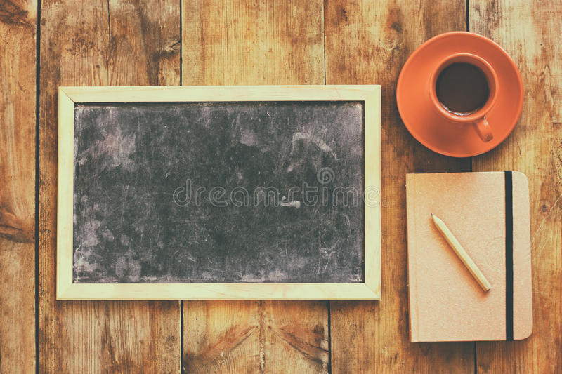 Top view image of empty blackboard next to cup of coffee and notebook, over wooden table. image with retro style filter.  stock photography