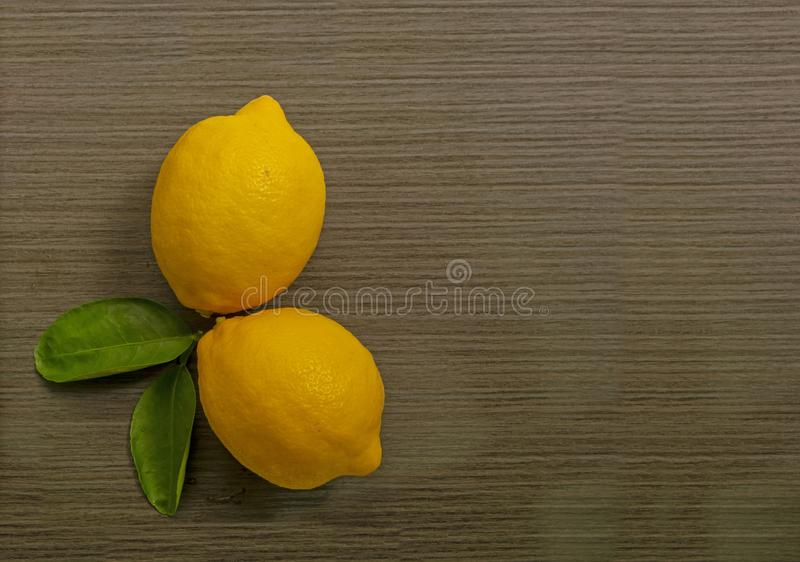 Top view image, Fresh yellow ripe lemon fruits and green leaf on brown wooden table. And copy space royalty free stock images
