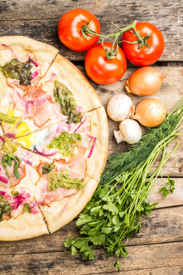 Top view image of half of pizza with vegetables around. stock photography