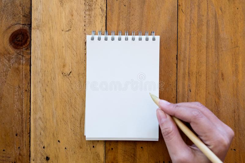 Top view image of a hand holding a pen and going to write on a blank white notebook stock images