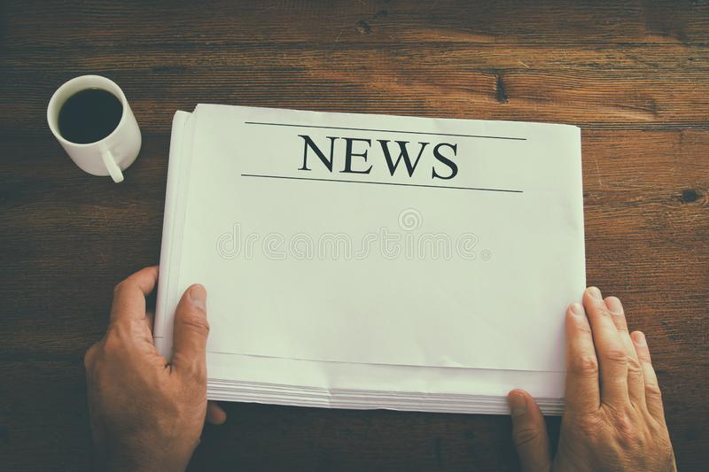 top view image of male hand holding blank Newspaper with empty space to add news or text. retro style image. royalty free stock photography
