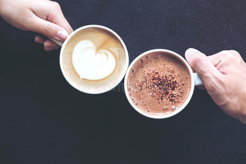 Top view image of man and woman`s hands holding coffee and hot chocolate cups stock images