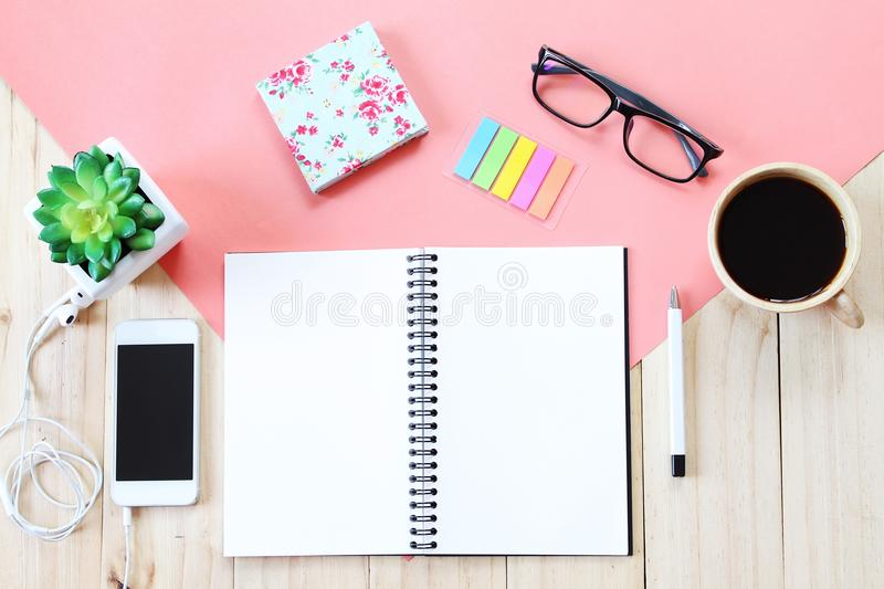 Top view image of open notebook with blank pages, accessories and coffee cup on wooden background, ready for adding or mock up. Still life, business, office stock image