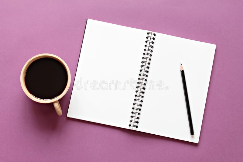 Top view image of open notebook with blank pages and coffee cup on color background, ready for adding or mock up. Still life, business, office supplies or royalty free stock images