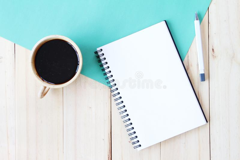 Top view image of open notebook with blank pages and coffee cup on wooden background, ready for adding or mock up. Still life, business, office supplies or stock image