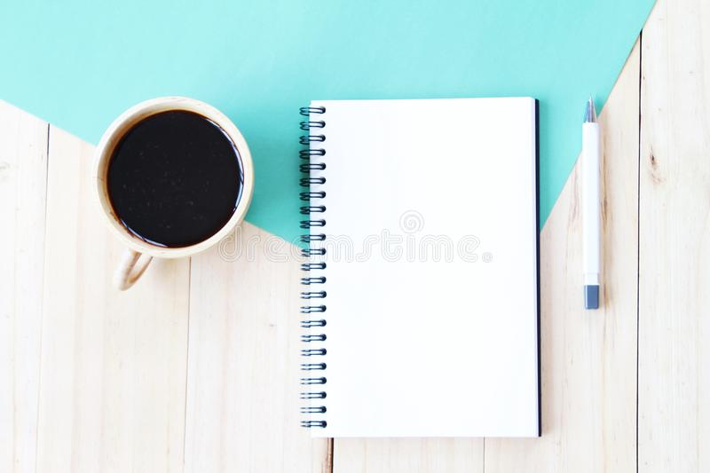 Top view image of open notebook with blank pages and coffee cup on wooden background, ready for adding or mock up. Still life, business, office supplies or royalty free stock photography