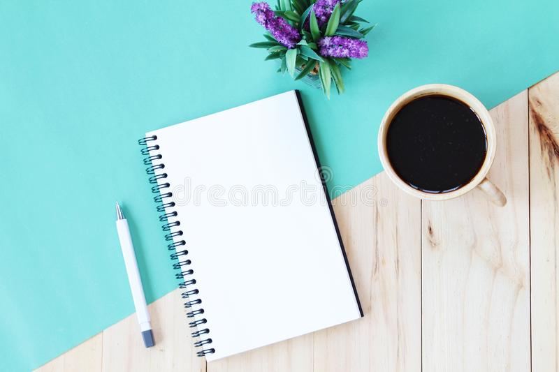 Top view image of open notebook with blank pages and coffee cup on wooden background, ready for adding or mock up. Still life, business, office supplies or royalty free stock image