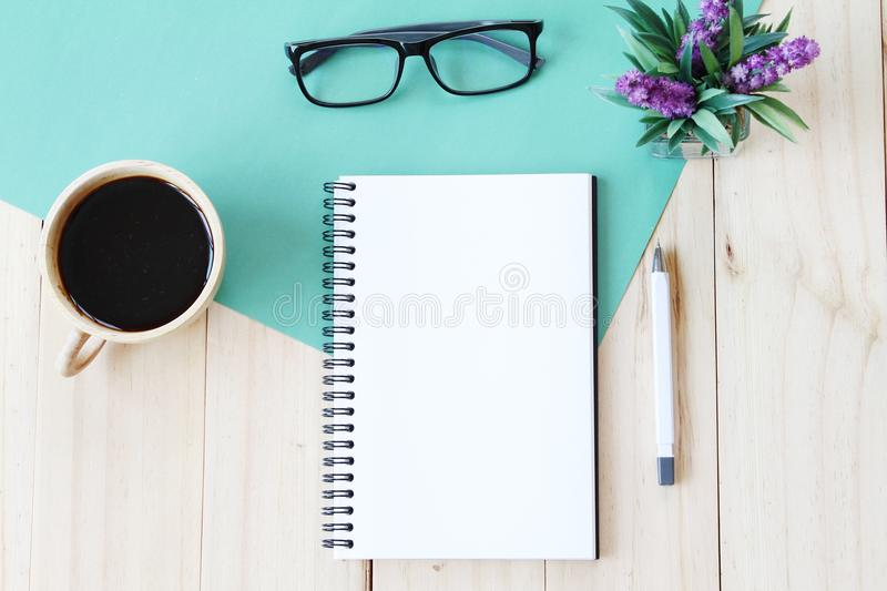 Top view image of open notebook with blank pages and coffee cup on wooden background, ready for adding or mock up. Still life, business, office supplies or stock photo