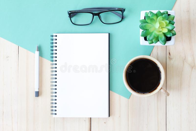 Top view image of open notebook with blank pages and coffee cup on wooden background, ready for adding or mock up. Still life, business, office supplies or stock photography
