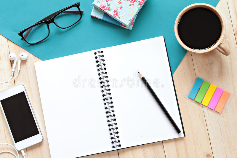 Top view image of open notebook with blank pages, mobile phone and coffee cup on wooden background, ready for adding or mock up. Still life, business, office stock photo