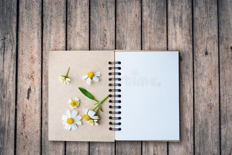 Top view image of open notebook with blank pages next to chamomile flower, on old wooden table. ready for adding text mockup. Top view image of open notebook royalty free stock photo
