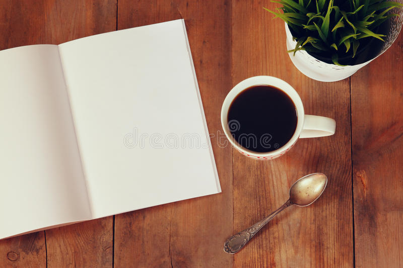 Top view image of open notebook with blank pages next to cup of coffe on wooden table. ready for adding text or mockup royalty free stock photography