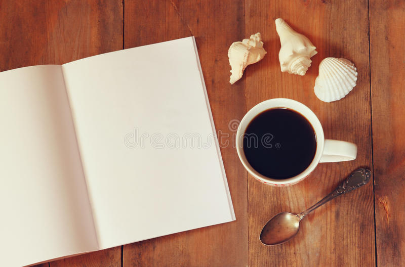 Top view image of open notebook with blank pages next to cup of coffe on wooden table. ready for adding text or mockup.  stock photos