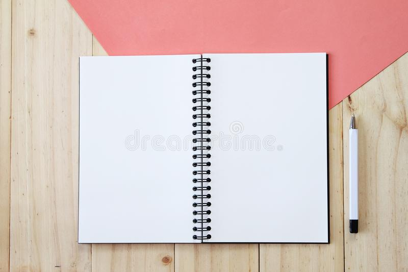 Top view image of open notebook with blank pages and pen on wooden background, ready for adding or mock up. Still life, business, office supplies or education royalty free stock image